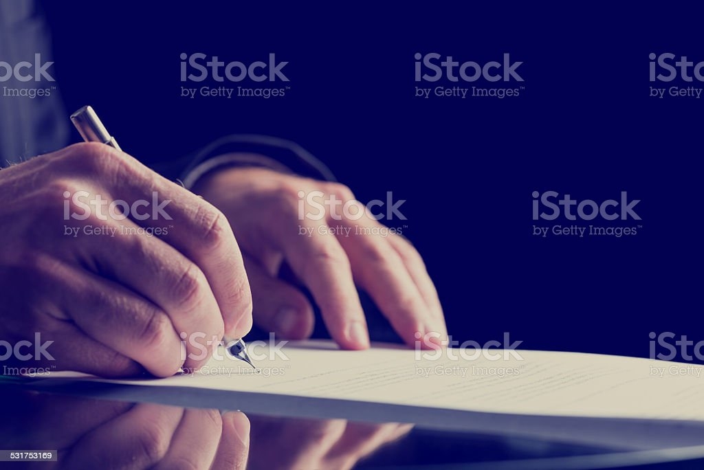 Close up Human Hand Signing on Formal Paper stock photo