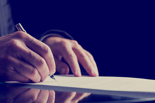 close up human hand signing on formal paper - testimonial stock photos and pictures