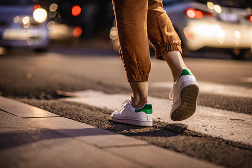 Photo of woman's legs on the zebra crossing