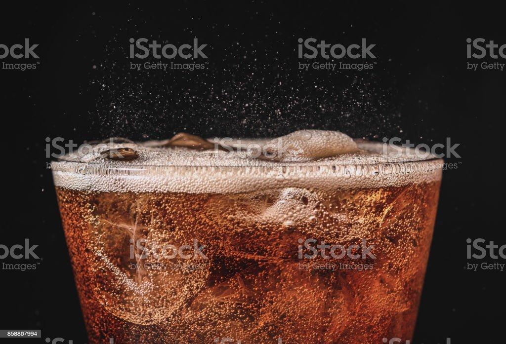 close-up cola de gelo no copo e bolha gasosa espirrando em fundo preto - foto de acervo