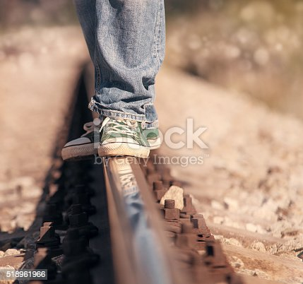 Close up image legs in sneackers on the railway
