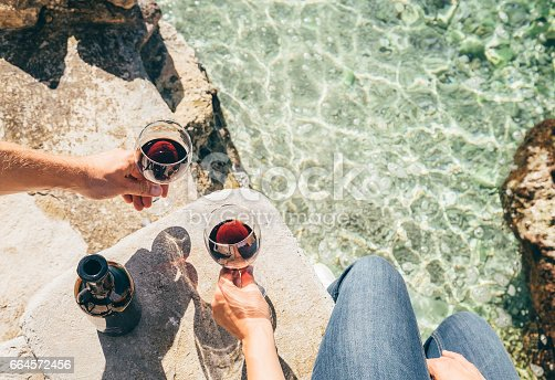 istock Close up image man and woman hands with goblet of wine at the sea side 664572456