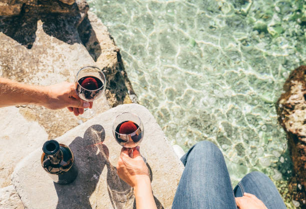 Close up image man and woman hands with goblet of wine at the sea side stock photo