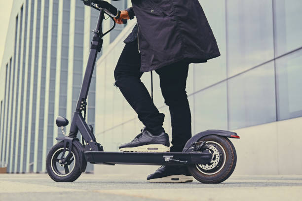 close up image of a man in the city - electric push scooter stock photos and pictures