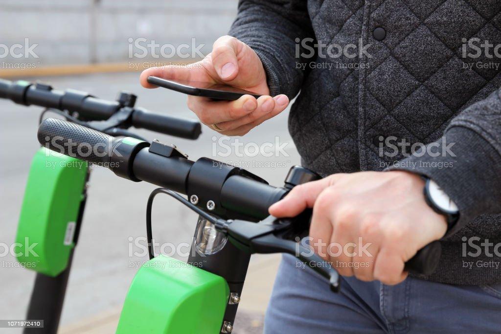 Schließen Sie herauf Bild eines Mannes auf ein Elektroroller online zu bezahlen – Foto
