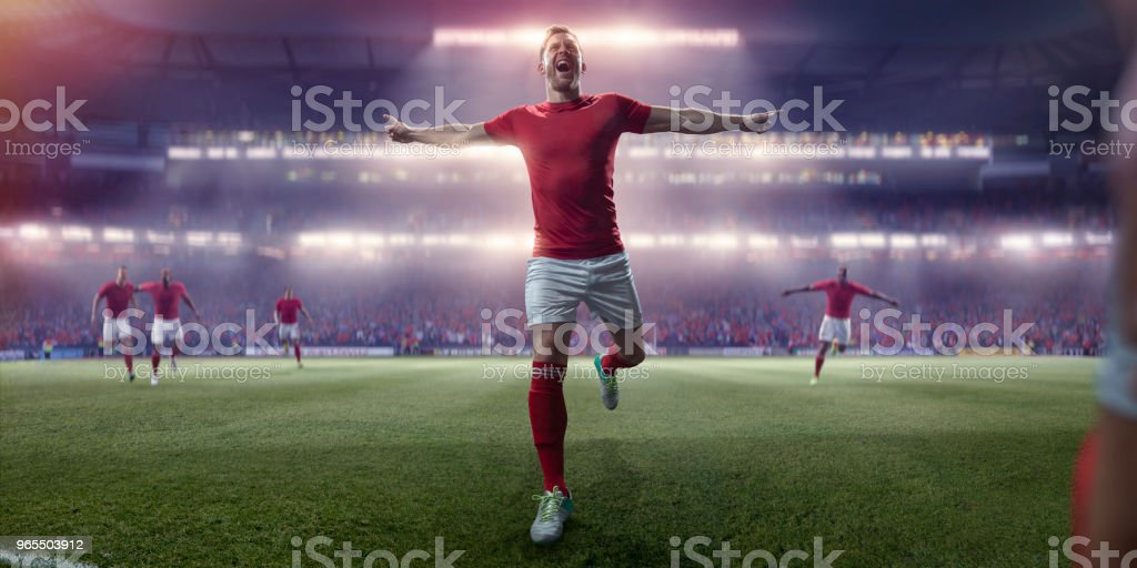 Professional Soccer Player Running With Arms Out In Victory Celebration stock photo