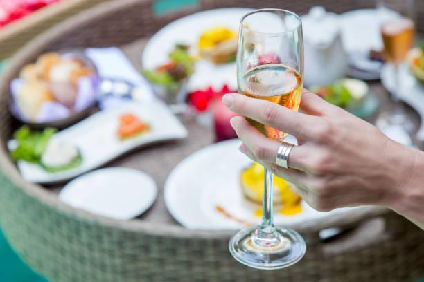 Nahaufnahme Bild einer Frau hält ein Glas Champagner, eine Mahlzeit neben dem Pool, FreizeitUrlaub Reise Sommerzeit Konzept – Foto