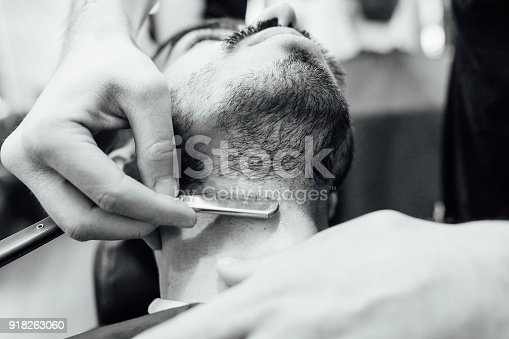 istock Close up image of barber makes beard cut of a man 918263060