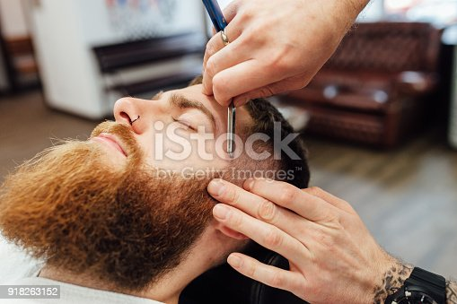 istock Close up image of barber makes beard cut of a man 918263152