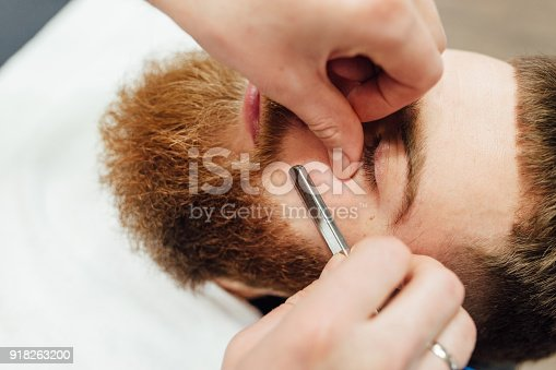 istock Close up image of barber makes beard cut of a man 918263200