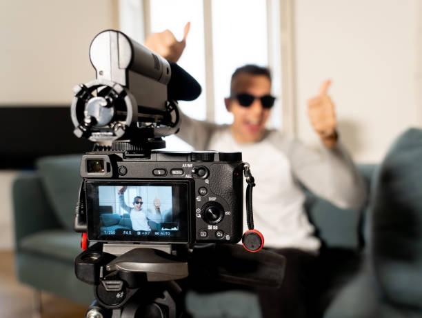Nahaufnahme Bild von Kamera-Bildschirm auf Stativ Aufnahme eines Video-Blog mit verschwommenen Young glücklich Mann auf seinen Zwanzigern auf dem Hintergrund. In Social Media vlog, netzwerk, – Foto