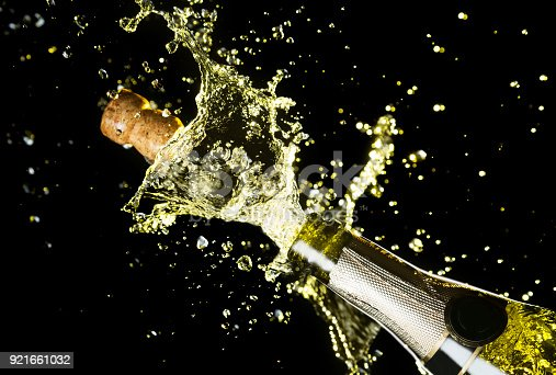 istock Close up image of champagne cork flying out of champagne bottle. Celebration theme with explosion of splashing champagne sparkling wine on black background. 921661032
