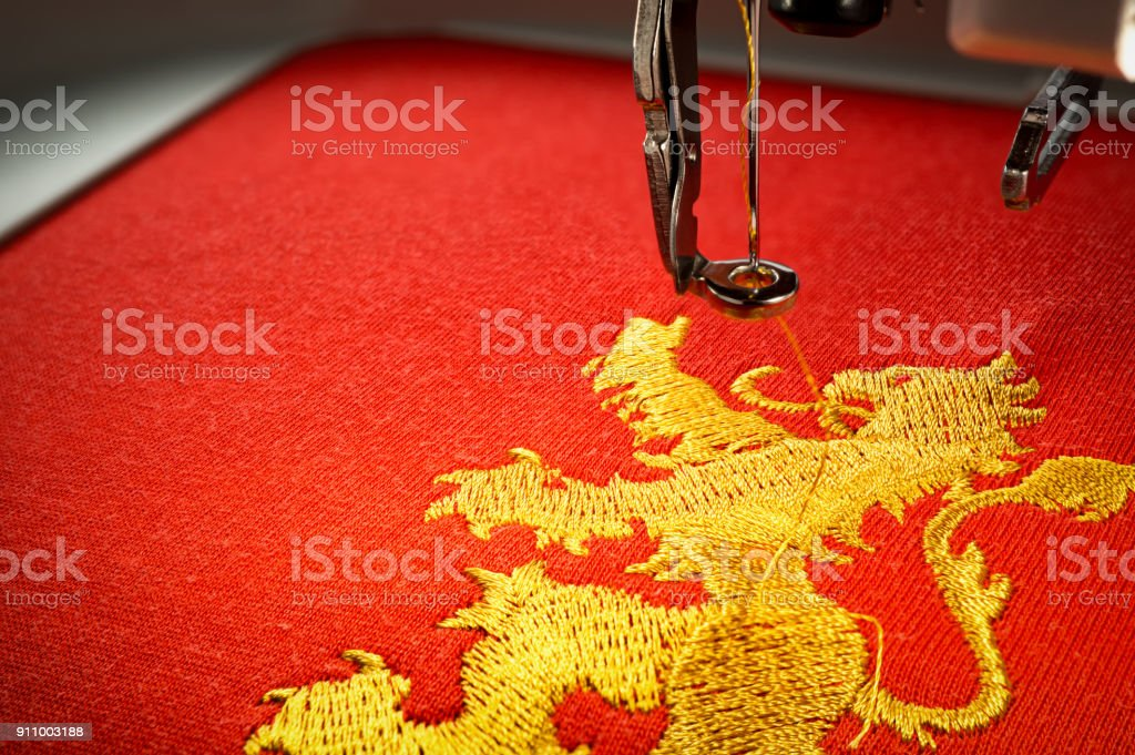 Close up image of embroidery machine and embroider gold lion on red fabric stock photo