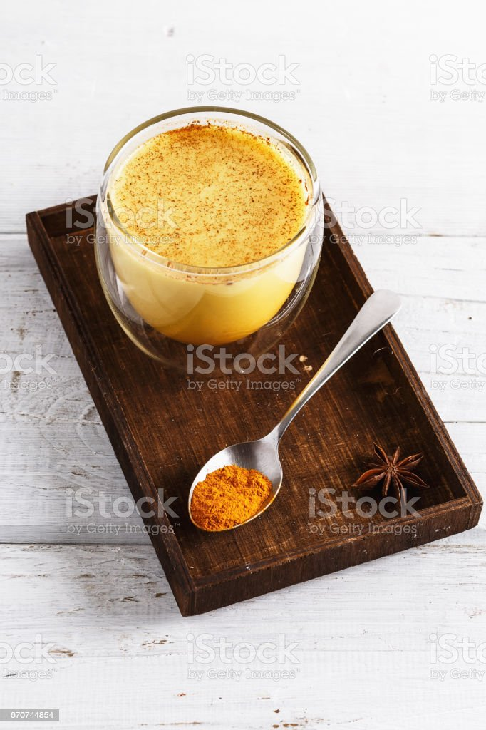 Close up image of golden latte over white wooden table stock photo