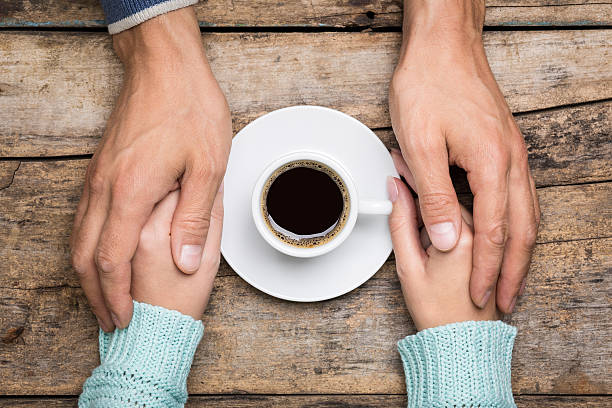 Close up image of people relations background Man holds woman's hand near a cup of coffee top view image on wooden backdrop. Friendship coffee background sergionicr stock pictures, royalty-free photos & images