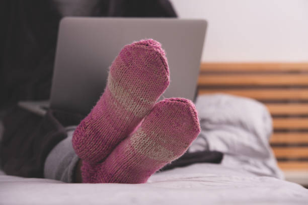Close up image of pink, purple warm socks on woman's legs at cozy winter. stock photo