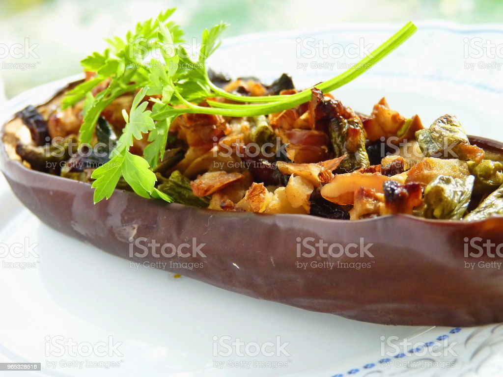 Close up image of stuffed aubergine on a white plate. Halved eggplant stuffed with mushrooms, vegetables and cheese. royalty-free stock photo