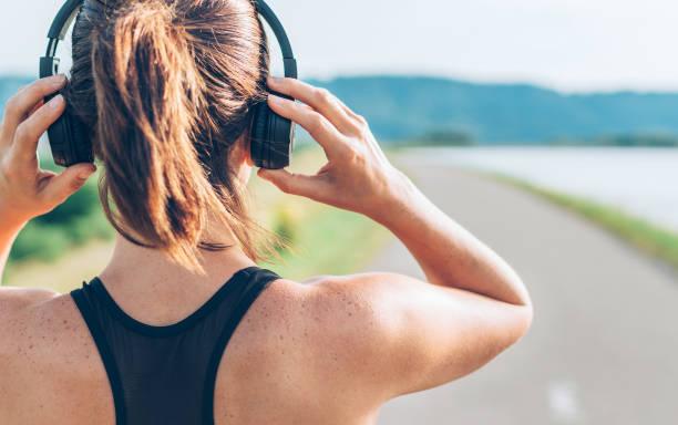 De cerca la imagen del adolescente ajustando auriculares inalámbricos antes de empezar a correr y escuchar música - foto de stock