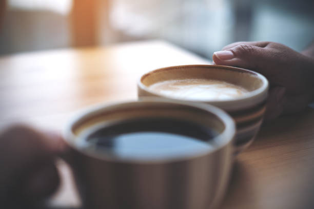 Close up image of two people clink coffee cups on wooden table in cafe stock photo