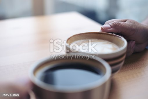 istock Close up image of two people clink coffee cups on wooden table in cafe 892742568