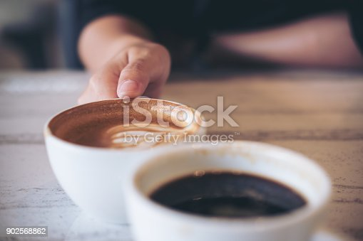 istock Close up image of two people clink white coffee mugs on wooden table in cafe 902568862