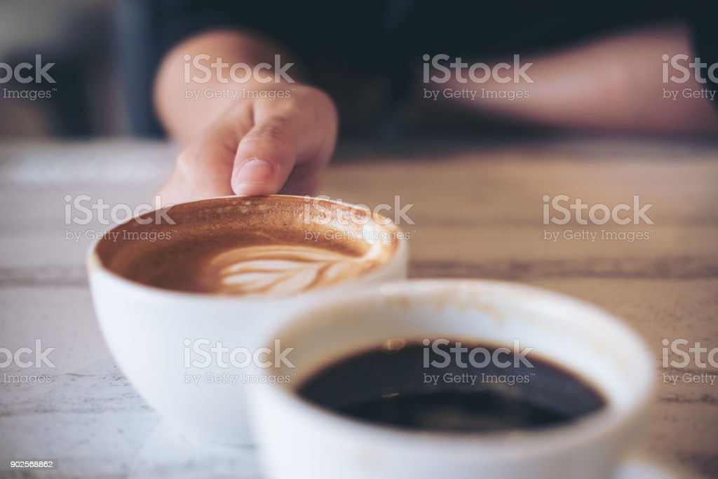 Close up image of two people clink white coffee mugs on wooden table in cafe stock photo