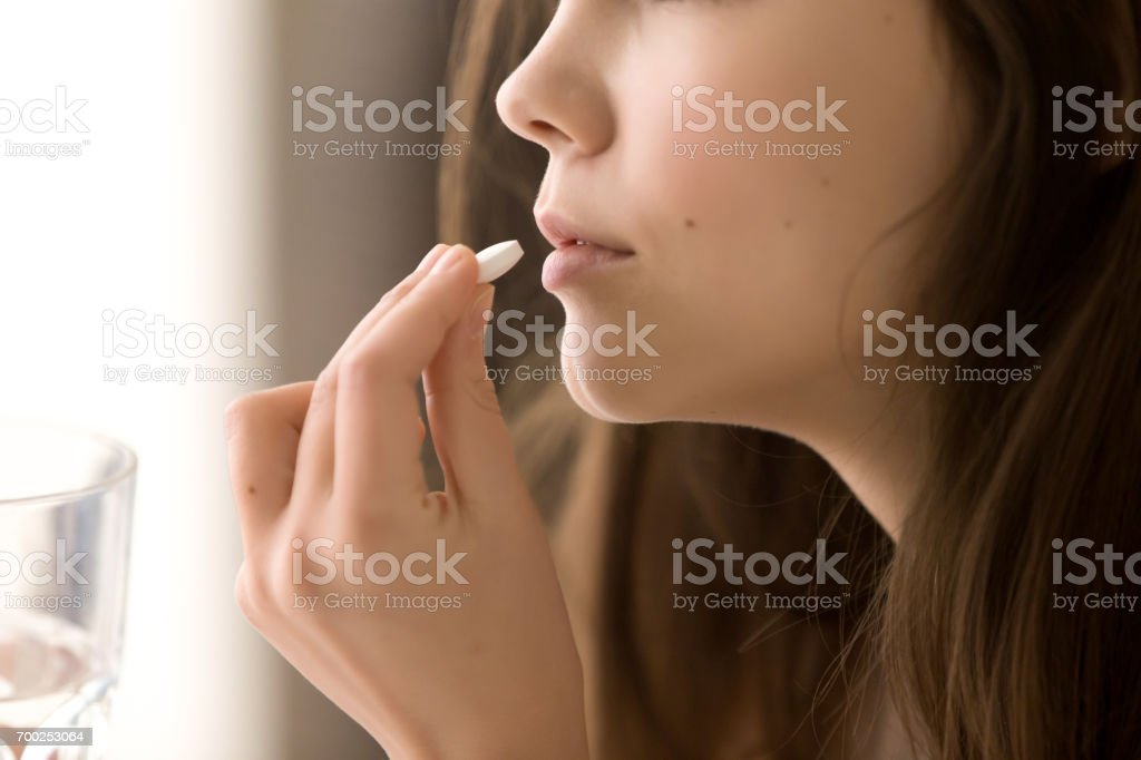Cerrar imagen de mujer tomando píldora blanca redonda foto de stock libre de derechos