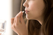 istock Close up image of woman drinking round white pill 700253064