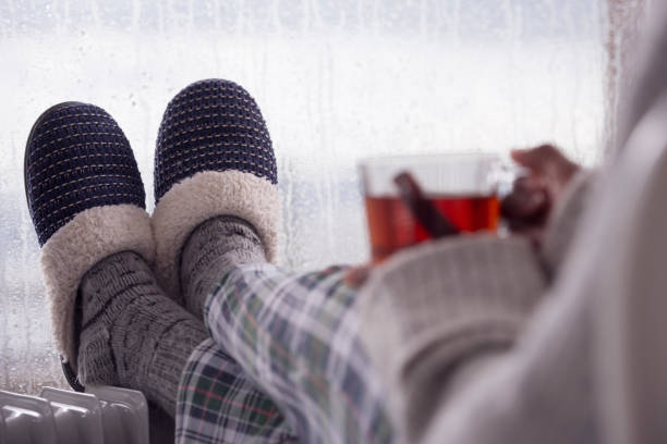 Close up image of woman's feet with slippers on radiator heater in the rainfall winter season. The woman drinking hot tea. stock photo