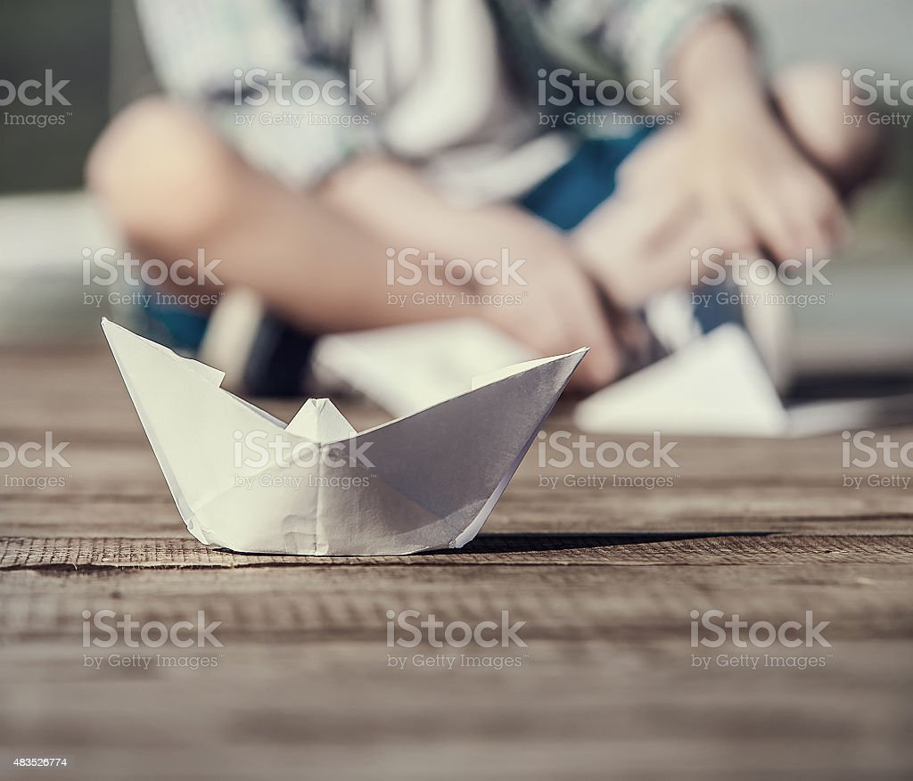 Close up image paper ship on the wooden pier stock photo