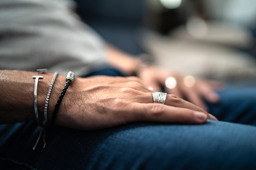 Close up in male hands with silver jewelry