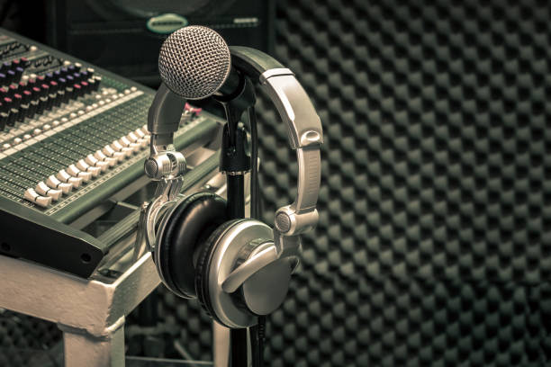 Close up instruments music background concept.Headphones hang  on microphone with sound mixer board in home recording studio.Free space for creative design text & wording mock up template wallpaper. stock photo