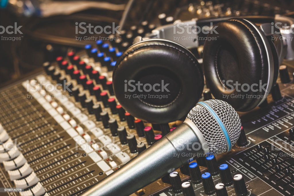 Close up instruments music background concept.Single microphone with headphones on sound mixer board in home recording studio.Free space for creative design text & wording mock up template. stock photo