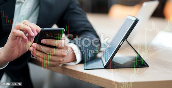 close up investor man holding smartphone for checking stock marketing an open tablet on table with double exposure candlestick graph , currency exchange trade concept