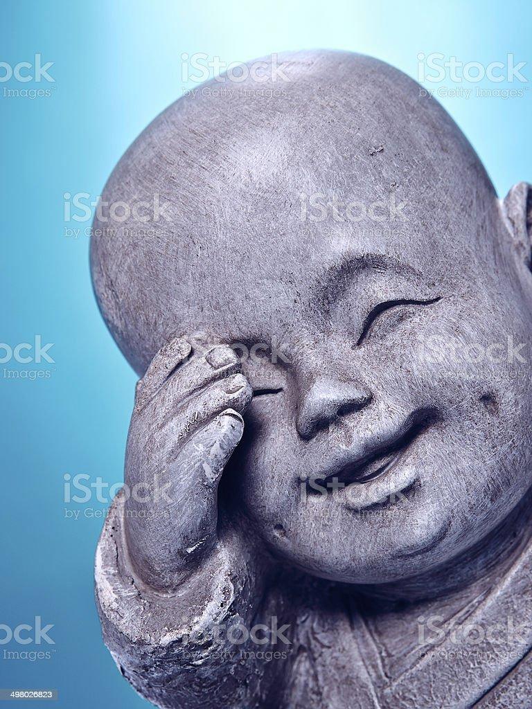Close Up Laughing Stone Buddah Isolated On Blue Background stock photo