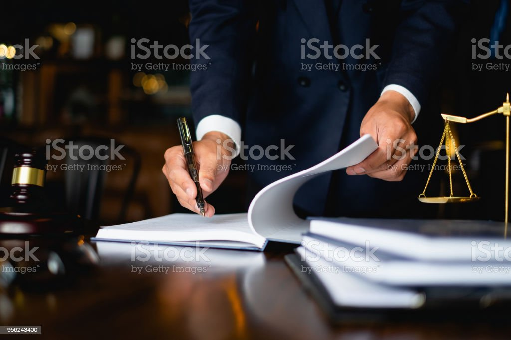 Close up lawyer businessman working or reading lawbook in office workplace for consultant lawyer concept. stock photo