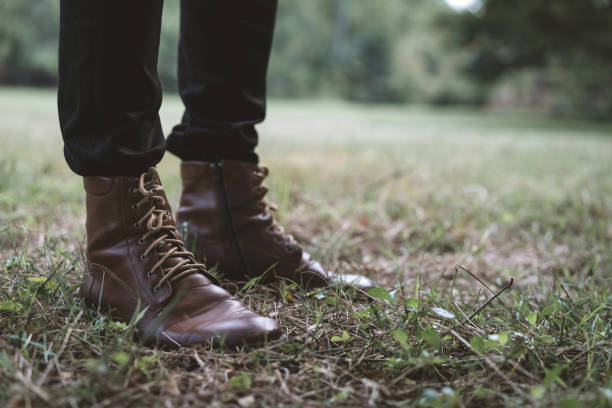 Close up leather boots of hipster man. Male legs in black jeans and brown leather shoes. concept of fashion and lifestyle. stock photo