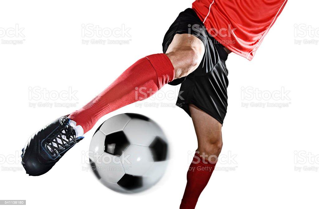 close up leg and shoe of football player kicking ball stock photo