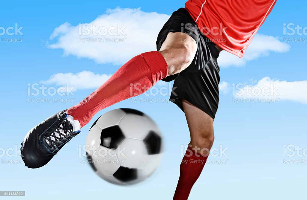 close up leg and shoe of football player kicking ball stock photo