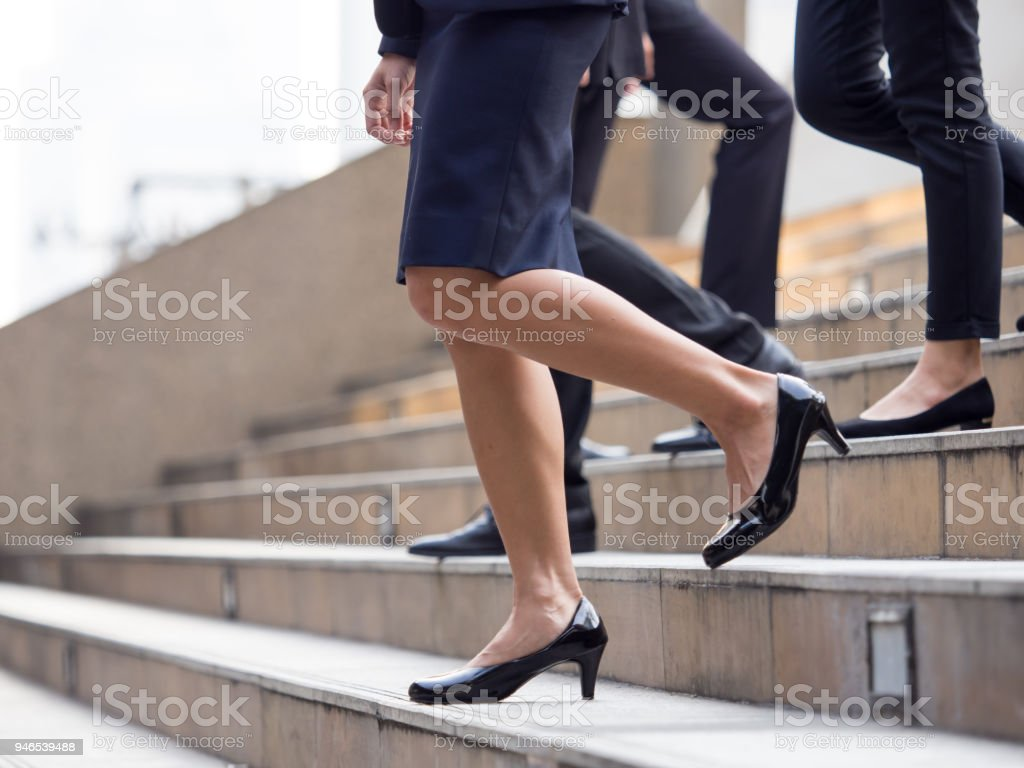 Close up legs of businessman and businesswoman in suit, walking down from stairs, go on business, go down, loss, retired, unemployment and quit from job concept stock photo