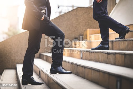 684803840istockphoto Close up legs of businessman walking stepping up stair in modern city, business growth, go up, success, grow up business concept 903164370
