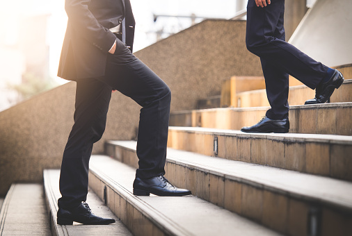 684803840 istock photo Close up legs of businessman walking stepping up stair in modern city, business growth, go up, success, grow up business concept 903164370