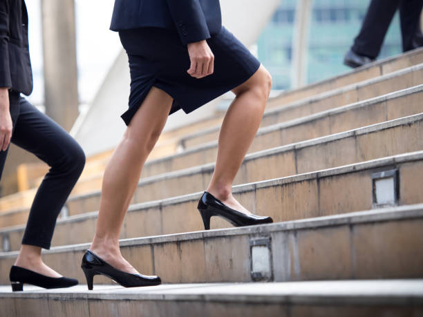 Close up legs of businesswoman walking stepping up stair in modern city, business growth, go up, success, grow up business concept stock photo