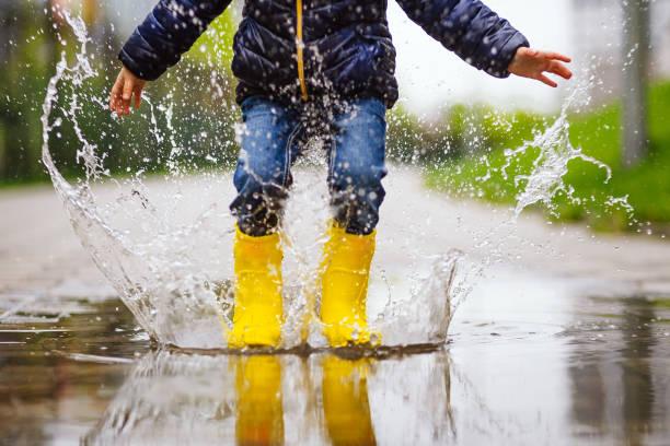 zbliżenie nóg dziecka z żółtymi gumowymi butami skacze w kałuży na jesiennym spacerze - deszcz zdjęcia i obrazy z banku zdjęć