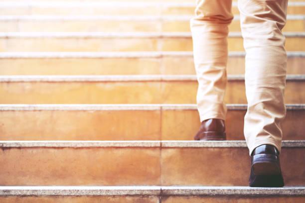 schließen beine schuhe des jungen geschäftsmannes eine person gehen schritt zu gehen die treppe in der modernen stadt, gehen nach oben, erfolg, wachsen. mit filter tones retro-vintage-warmeffekt. treppe - treppe stock-fotos und bilder
