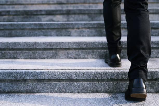 close-up benen schoenen van jonge zakelijke man één persoon lopen stap omhoog de trap op in de moderne stad, ga omhoog, succes, opgroeien. trap - zwarte spijkerbroek stockfoto's en -beelden