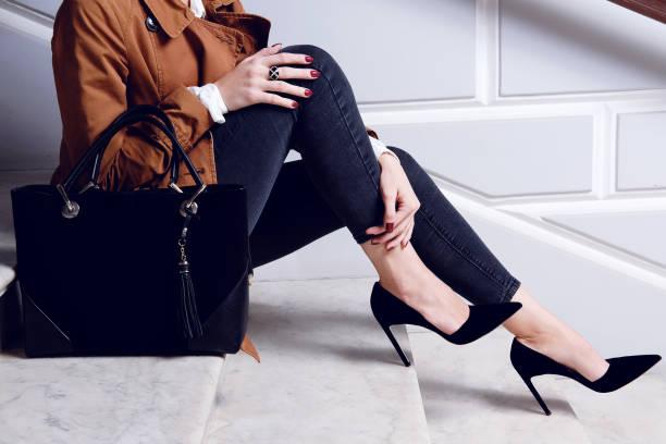 beine, die frau in schwarzen high heels schuhe sitzen auf weißer treppe hautnah. - handtasche jeans stock-fotos und bilder
