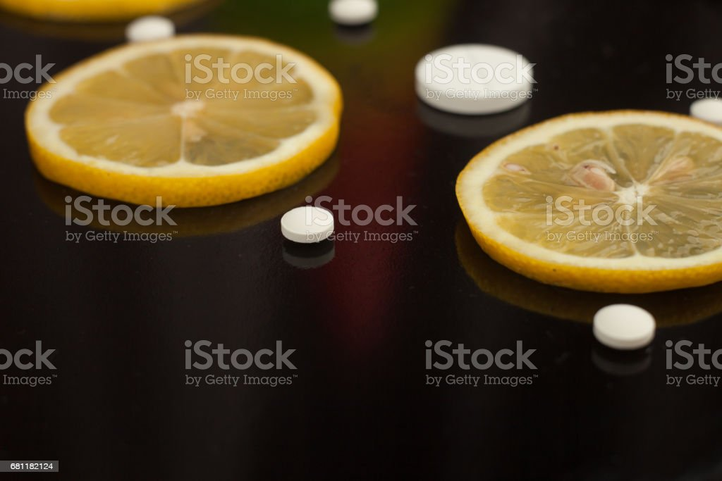 Close up, lemon slice and pills, flu medicine, front view, copy space royalty-free stock photo