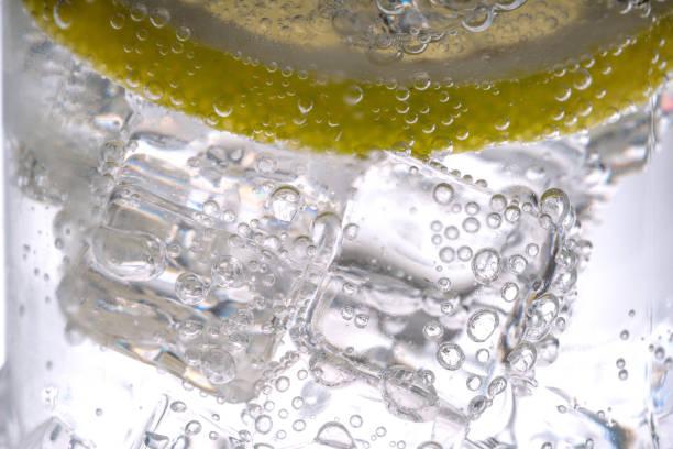 Gros plan des tranche de citron éclabousser dans l'eau gazeuse - Photo