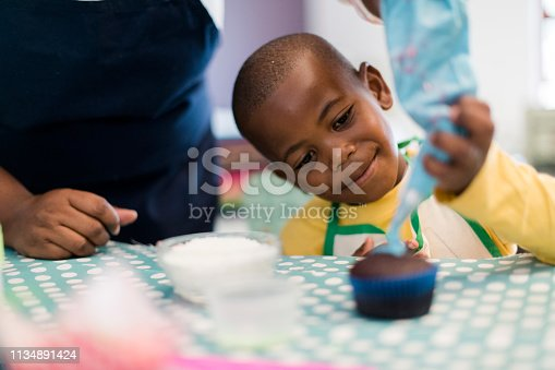 Close up little boy icing cupcake with the help of his mother